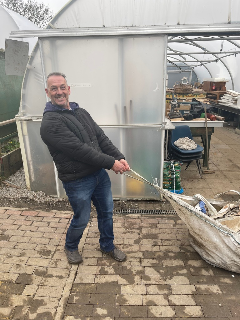 Outside polytunnel with building materials, laughing