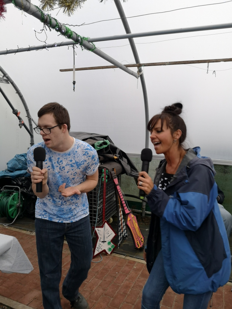 Having fun, singing in the polytunnels with a team member