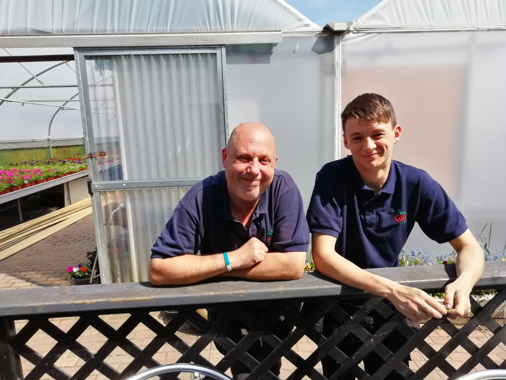 Outside polytunnels with a team member, sunny day and smiling